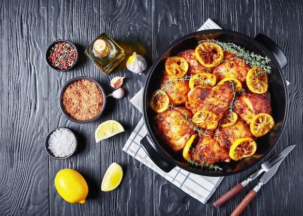 Вкусные куриные бедра с обжаренными ломтиками лимона и тимьяном в черной керамической посуде на деревянном столе, горизонтальный вид сверху, плоский, пространство для копирования