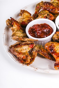 Delicious chicken wings on wooden table