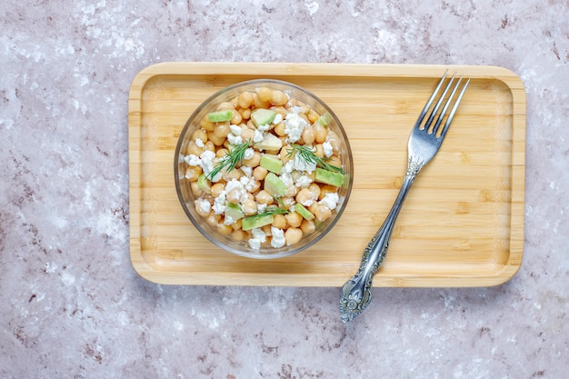 Delicious chickpea salad with avocado and feta cheese, top view