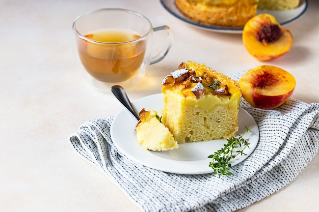 Delicious chiffon cake with custard cream and nectarines with herbal tea and thyme