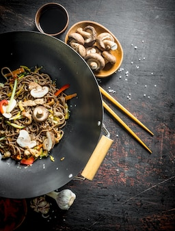 Delicious chinese soba wok noodles with beef, mushrooms and vegetables. on dark rustic surface