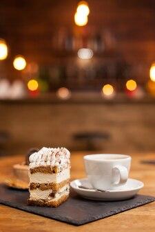 ホワイトクリームとシナモンをのせた美味しいチョコレートケーキ。おいしいコーヒーのカップ。美味しいデザート。新鮮な食材を使った伝統的なデザート。