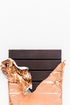 Delicious chocolate bar wrapped in golden foil on white background