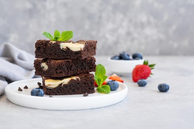 Вкусный шоколадный чизкейк со свежими ягодами и мятой на тарелке на сером фоне