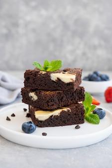 Вкусный шоколадный чизкейк со свежими ягодами и мятой на белой тарелке на сером фоне бетона. скопируйте пространство.
