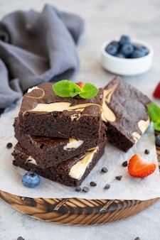 나무 판자에 신선한 딸기와 민트를 넣은 맛있는 초콜릿 브라우니 치즈 케이크