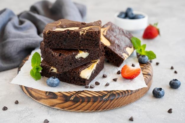 新鮮なベリーとミントが入ったおいしいチョコレートブラウニーチーズケーキ