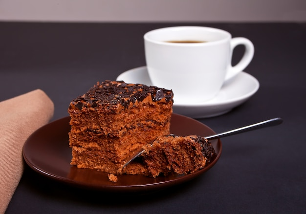 Delicious chocolate cake on the brown plate with cup of coffee on the black table
