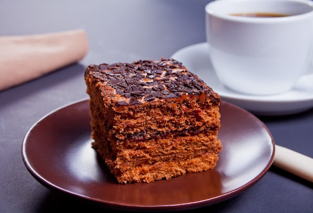 Delicious chocolate cake on the brown platewith cup of coffee on the black table