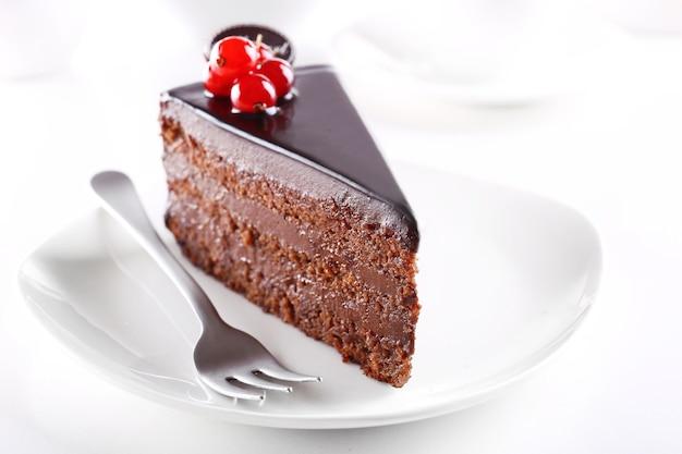 明るい背景のテーブルの上のプレート上のおいしいチョコレートケーキ