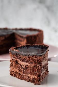 大理石の背景にテーブルの上の皿においしいチョコレートケーキ。ペストリーカフェやカフェメニューの壁紙。垂直。