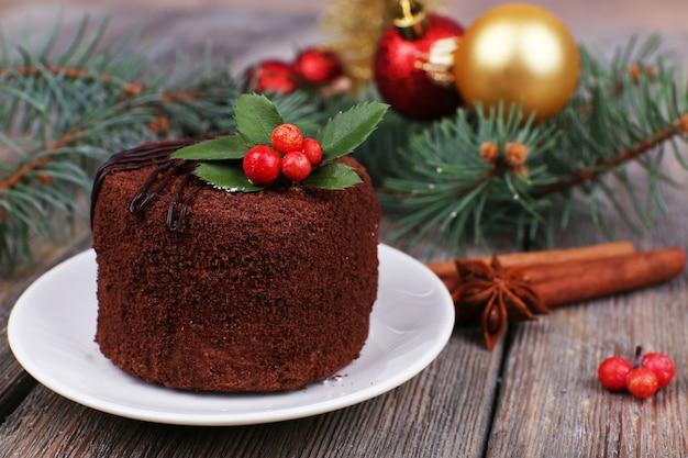 Вкусный шоколадный торт на блюдце с падубом и ягодами на рождественском украшении и деревянном столе