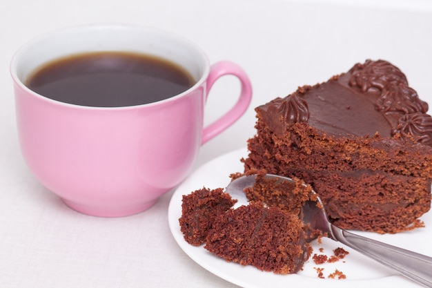 Delicious chocolate cake on plate with pink cup of coffee on table on light background