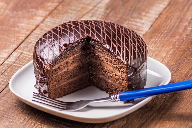 Delicious chocolate cake on a plate under wooden background.