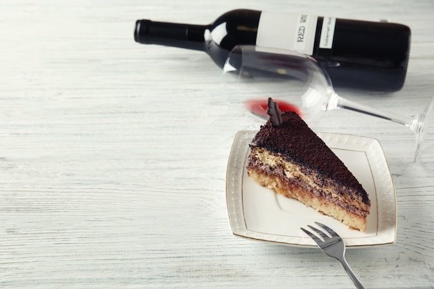Delicious chocolate cake and red wine on white wooden table