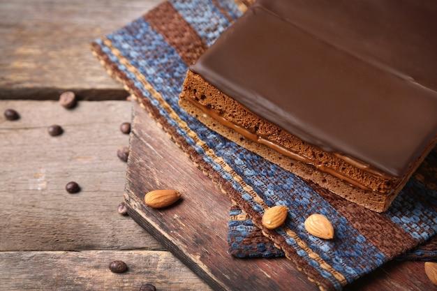 木製の背景にコーヒー豆とおいしいチョコレートケーキ