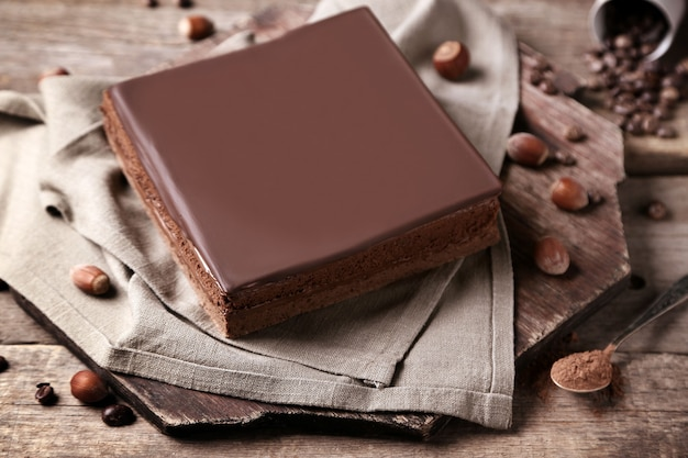 Delicious chocolate cake with coffee beans on wooden background