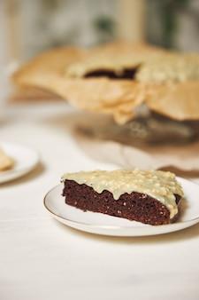 미적 세부 사항으로 제시된 흰색 테이블에 크림과 함께 맛있는 초콜릿 케이크