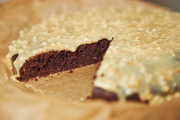 美的ディテールを提示した白いテーブルの上のクリームとおいしいチョコレートケーキ