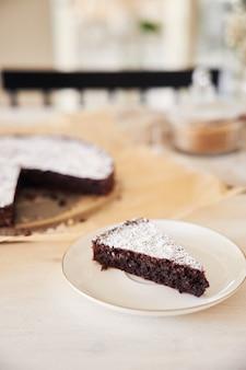 미적 세부 사항이 있는 흰색 테이블에 크림을 넣은 맛있는 초콜릿 케이크