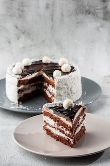 大理石の背景にテーブルの上の皿に白いココナッツクリームとおいしいチョコレートケーキ。ペストリーカフェやカフェメニューの壁紙。垂直。