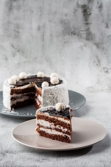 Delicious chocolate cake with white coconut cream on plate on table on marble background. wallpaper for pastry cafe or cafe menu. vertical.