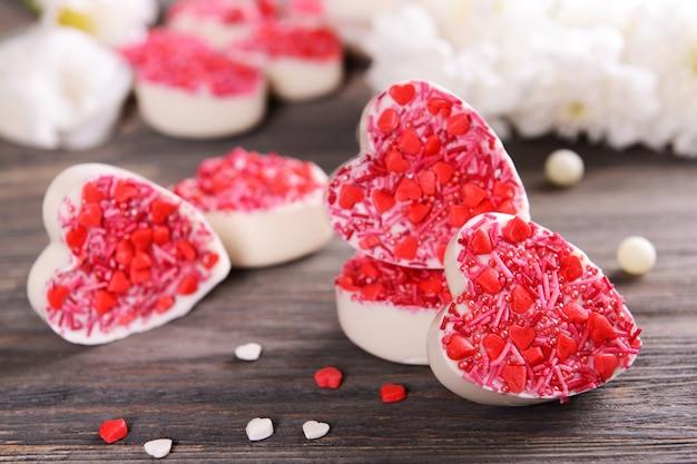 Вкусные шоколадные конфеты в форме сердца на крупном плане стола