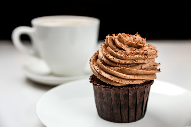A delicious chocolate cupcake with cream and a cup of cappuccino coffee