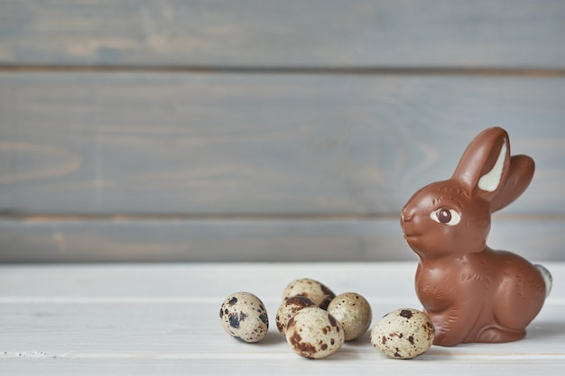 Delicious chocolate easter bunny and eggs on wooden table