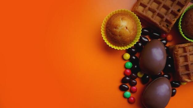 オレンジ色の背景においしいチョコレートのイースターエッグ、ワッフル、お菓子