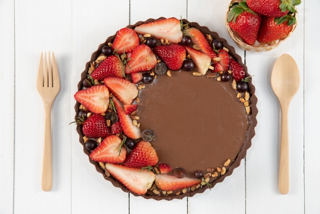 Delicious chocolate homemade tart decorated with fresh fruits.