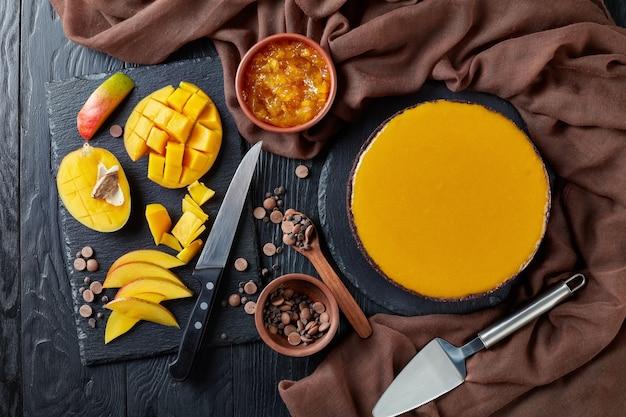 茶色の布、新鮮な甘いマンゴーとケーキシャベル、上からの眺め、フラットレイと黒い木製のテーブルの上のおいしいチョコレートマンゴーチーズケーキ
