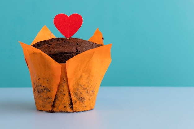 파란색 테이블에 붉은 마음과 청록색 배경이 있는 맛있는 초콜릿 머핀. 복사 공간