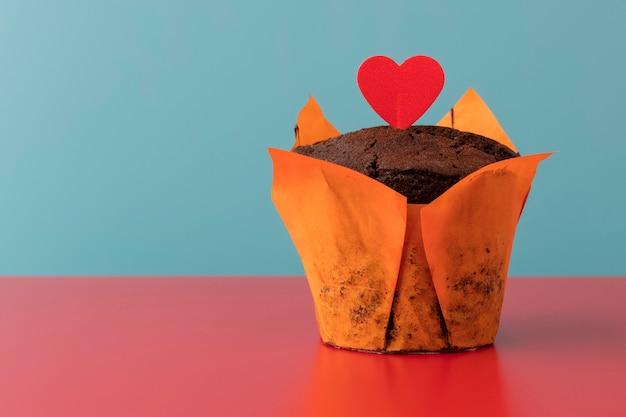빨간 테이블에 빨간 하트와 오렌지 배경이 있는 맛있는 초콜릿 머핀. 복사 공간