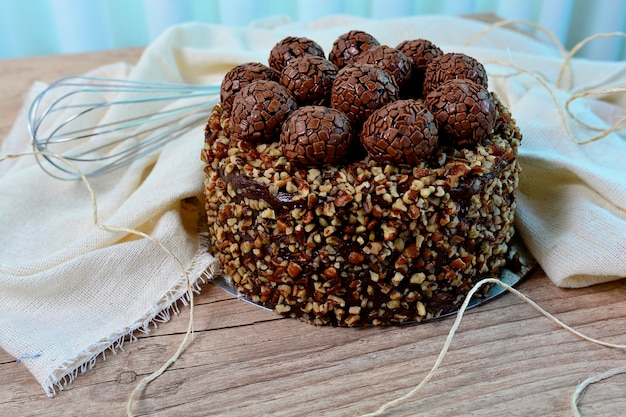 Delicious chocolate nuts cake with  chocolate truffle topping on a rustic table