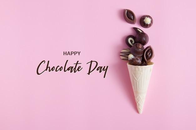 ピンクの表面にワッフル コーンのおいしいチョコレート プラリネと碑文の幸せなチョコレートの日