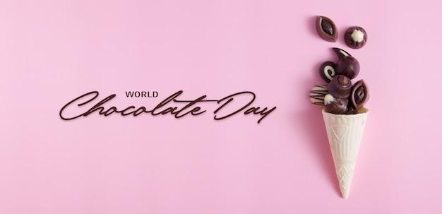 Вкусные шоколадные конфеты в вафельном рожке на розовой поверхности с надписью всемирный день шоколада