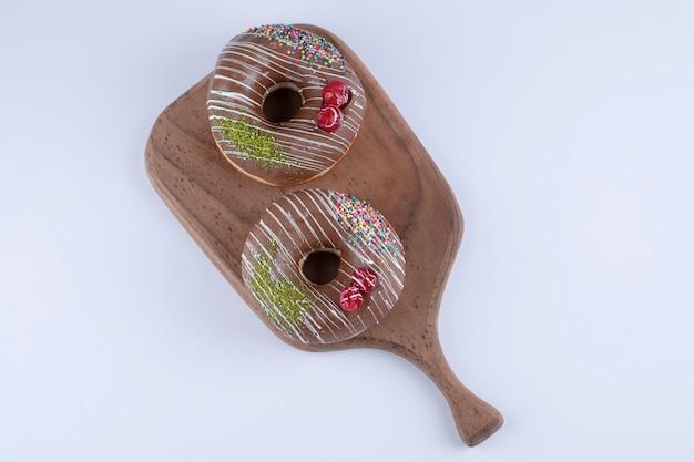 Delizioso cioccolato spruzza ciambelle sul tagliere di legno.