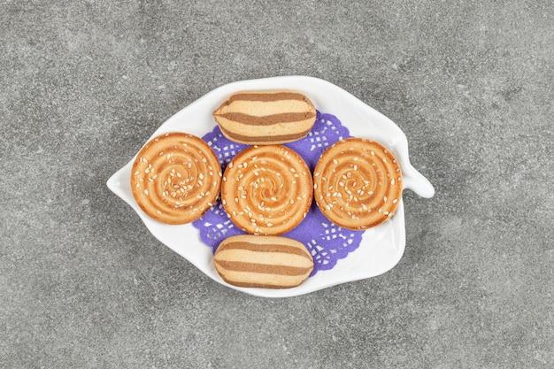 하얀 접시에 맛있는 초콜릿 스트라이프 비스킷과 참깨 비스킷