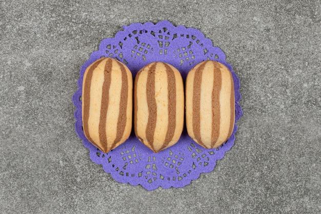 Deliziosi biscotti al cioccolato a strisce sul tovagliolo blu