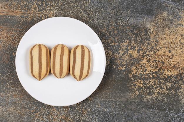 白い皿に美味しいチョコレートストライプビスケット。