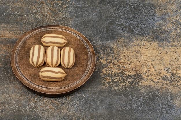 木の板に美味しいチョコレートストライプビスケット。