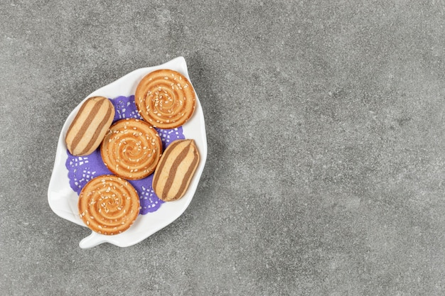 Deliziosi biscotti al cioccolato a strisce e biscotti al sesamo sul piatto bianco