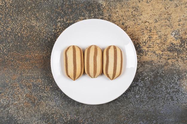 Deliziosi biscotti al cioccolato a strisce sulla zolla bianca.