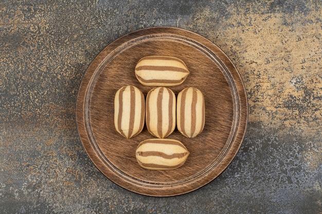 Deliziosi biscotti al cioccolato a strisce sul piatto di legno.