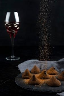 黒の背景に美味しいチョコレートトリュフと赤ワイン。