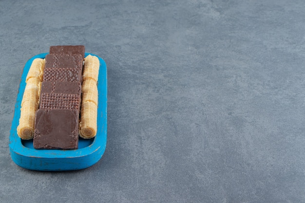Delicious chocolate and waffle rolls on blue plate.