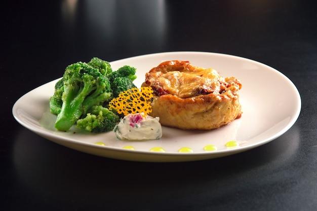브로콜리와 부드러운 치즈 소스와 함께 치킨 필레에서 맛있는 다진 스테이크