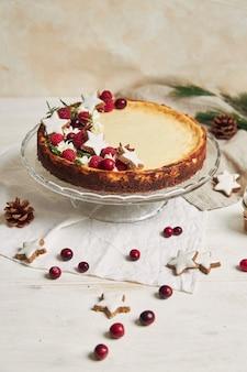 Deliziosa cheesecake natalizia con mirtilli rossi e stelle di biscotti su un tavolo bianco