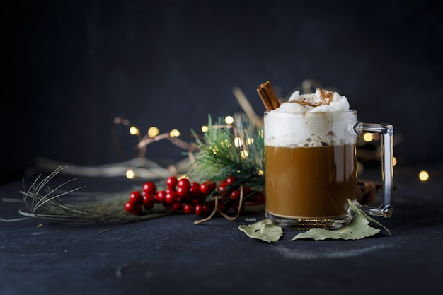 Delizioso caffè natalizio con cannella e schiuma, accanto agli agrifogli su una superficie scura